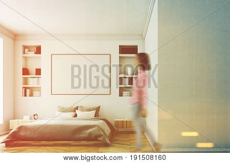 Woman in a modern luxury bedroom with white walls a large bed in the center of the room two bookcases a large window and a framed horizontal poster. 3d rendering mock up toned image