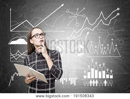 Portrait of a nerdy girl in glasses standing near a blackboard with different graphs and diagrams on a blackboard