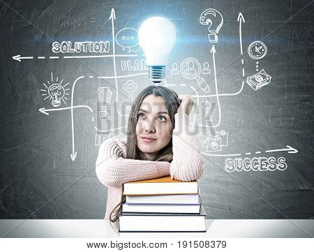 Young woman wearing a pink sweater and sitting at a white table with a pile of colorful book. She is dreaming near a blackboard with a business scheme and a blue light bulb above her head.
