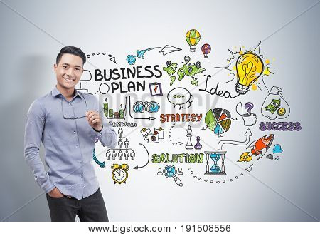 Portrait of a smiling Asian businessman wearing a blue shirt and dark trousers and holding glasses. Concrete wall background with a colorful light business plan sketch.