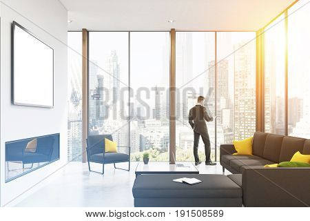 Rear view of a businessman standing near a panoramic living room window and looking at his smartphone screen. There is a gray sofa and a large coffee table. 3d rendering mock up toned image