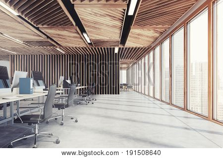 Side view of an open space office interior with wooden walls concrete floor and two rows of computer tables along a wall and a panoramic window. 3d rendering mock up toned image