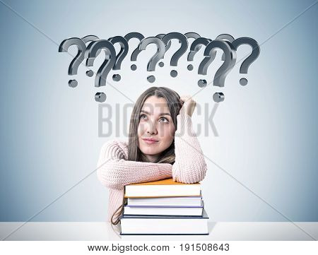 Portrait of a young woman wearing a pink sweater and sitting at a white table with a pile of colorful book. She is dreaming near a concrete wall with many gray question marks.