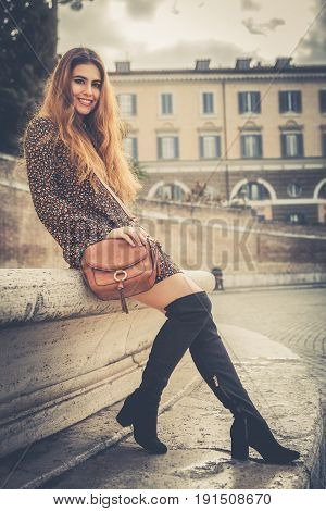 Attractive and fashionable smiling young woman. Outdoors in the city center. The beautiful girl is sitting on a wall and with a handbag and shoes high boots. A palace behind her.