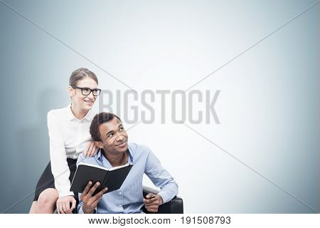 Portrait of a smiling African American man wearing a blue shirt and a young blond woman wearing glasses and sitting on a leather armchair near him. Mock up