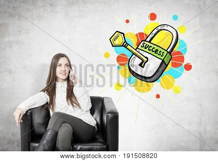 Young businesswoman with fair hair smiling and sitting in a leather armchair and talking on her smartphone. Concrete wall with a key to success sketch