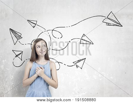 Portrait of a dreamy teen girl wearing a blue dress and standing with her hands near the heart and looking upwards near a concrete wall with paper plane icons on it
