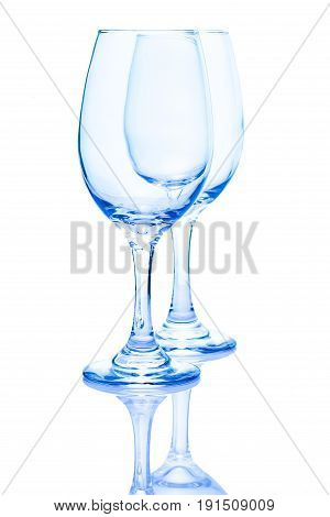 A pair of light blue wine glasses isolated on white with a reflection