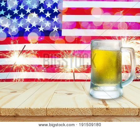 Glass of beer on wooden table. USA flag with sparklers background celebrate American Independence Day of 4th July