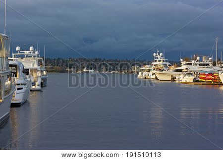 Lake Union panorama with yachts and boats in Seattle USA. Sunset over Lake Union with dark clouds on the horizon.