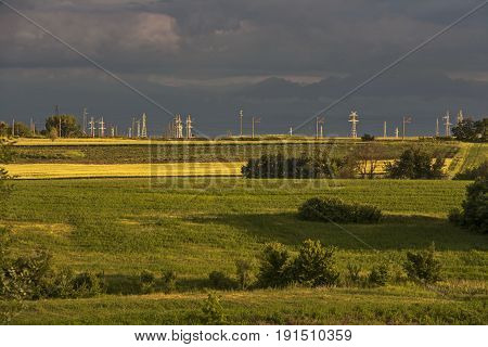 Fields with high voltage poles illuminated by sunset