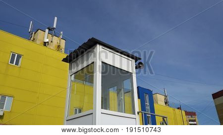 cabin with a loudspeaker on the background of yellow-and-blue buildings and the sky.