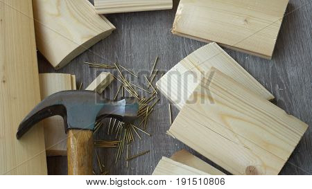 composition of boards, nails and hammer, hand hammer puts in the frame.