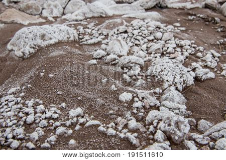 White Mineral Deposit Clings ot Rocks In Muddy Wash in desert