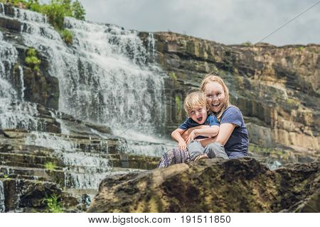 Mother And Son Hikers, Tourists On The Background Of Amazing Pongour Waterfall Is Famous And Most Be