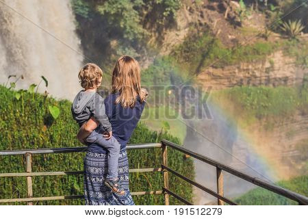 Mom And Son On The Background Of Majestic Landscape Of Elephant Waterfall In Summer At Lam Dong Prov