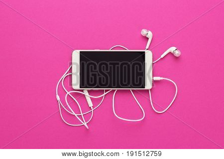 studio shot of smartphone and earbuds on purple background. top view of white smartphone and headphones. smartphone with white headset over bright pink. view from above of smartphone on bright colored back