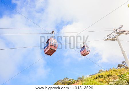 GENTING HIGHLANDS, MALAYSIA - APRIL 16, 2017: Tourists travel on cable car of Genting Skyway on April 16, 2017 in Malaysia. It is a gondola lift connecting Gohtong Jaya and Resorts World Genting.