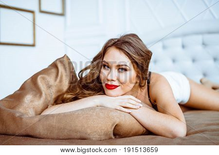 fashion photo of sexy brunet curly woman in lace lingerie and stockings with a belt posing on a luxurious bedspread and cushions