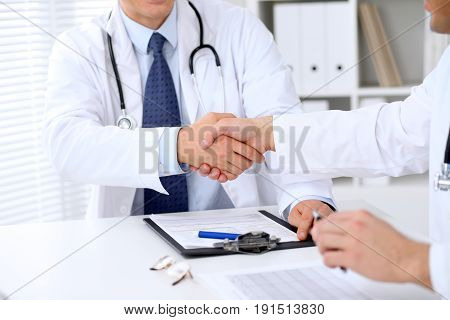 Two doctors shaking hands to each other sitting at the table in hospital office.