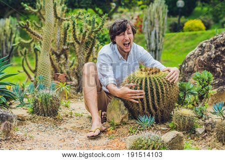 A Man Is Sitting Among Large Cacti. Pain Concept