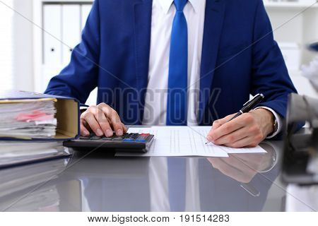 Close up view of bookkeeper or financial inspector hands making report, calculating or checking balance. Internal Revenue Service inspector checking financial document
