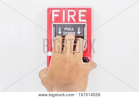 Hand of man pulling fire alarm switch on the white wall as background for emergency case at the new factory building.