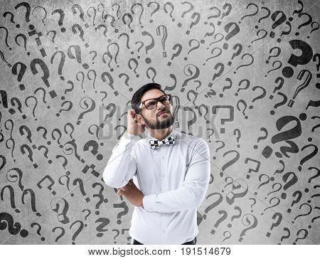 Confused businessman looking up in front of wall with question marks