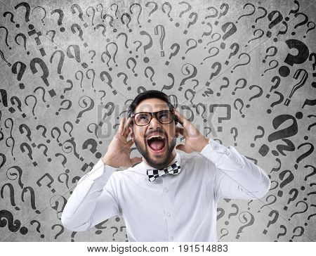 Shocked and confused businessman looking up in front of wall with question marks