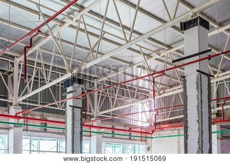 Ventilation pipes in silver insulation material and fire sprinkler on red pipe are hanging from the ceiling inside new building.