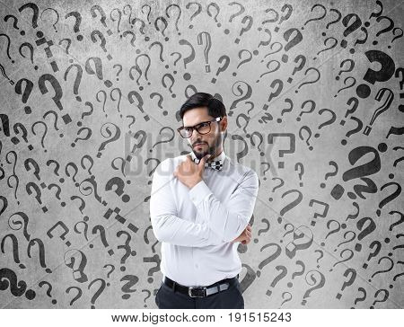 Thoughtful businessman standing in front of wall with question marks sign