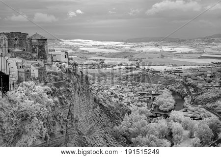 Infrared view of the hillside looking down of the white hilltop town of Arcos de la Frontera Cadiz Spain