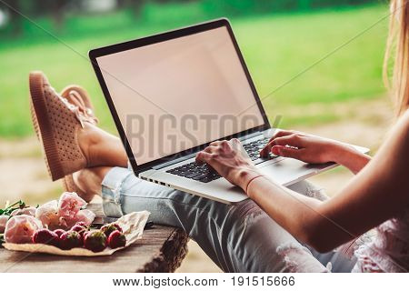 Young woman using and typing laptop computer at rough wooden table with coffee cup strawberries bouquet of peonies flowers smartphone. Freelancer working in outdoor park. Toning