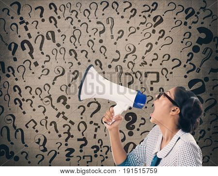 Businesswoman shouting on megaphone with question marks on wall