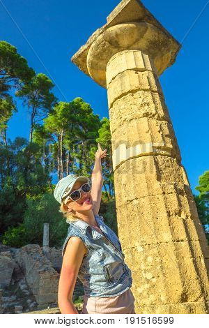Smiling and happy traveler woman shows a column with capital in Ancient Olympia, Peloponnese, Greece. Mediterranean travel destination enjoying. Female tourist in Unesco Archaeological Site Heritage.
