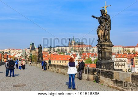PRAGUE, CZECH REPUBLIC - APRIL 14, 2016: Charles Bridge (Karluv Most) and Old Town Tower at blue sky Prague Czech Republic.This bridge is the oldest in the city and a very popular tourist attraction.