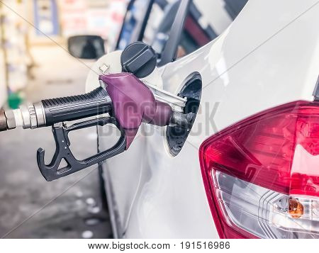 Fuel nozzle to add fuel in car at petrol station.