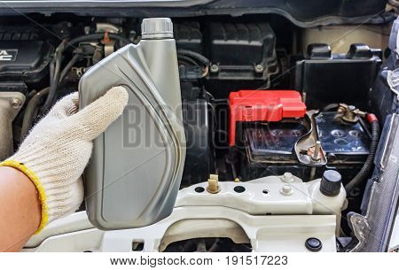 Auto mechanic hand holding motor oil Car maintenance
