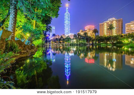 Lakeside scenery of Taipei 101 Tower among skyscrapers in Xinyi District Downtown at night with view of reflections on the pond in an urban park ~ Romantic nightscape of Taipei city under gloomy sky