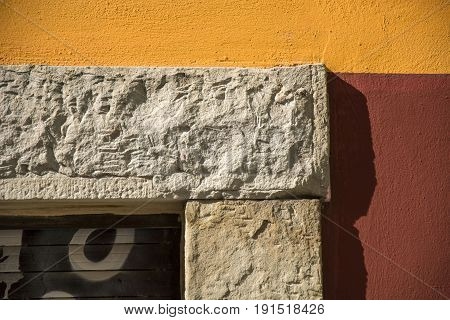 Photo of a facade detail with several colours and sunlight