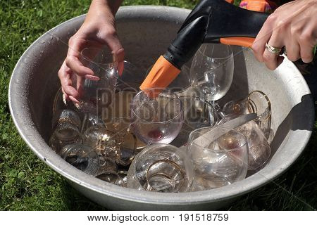 Female hands with garden hose washing wine glasses placed in basin with water