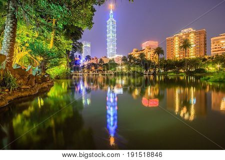 Lakeside scenery of Taipei 101 Tower among skyscrapers in Xinyi District Downtown at night with view of reflections on the pond in an urban park ~ Romantic nightscape of Taipei city