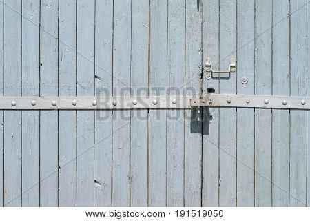 Old painted wooden garage door of grey color