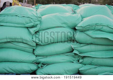 Closeup of green sandbags on blue pallet with blurred background.