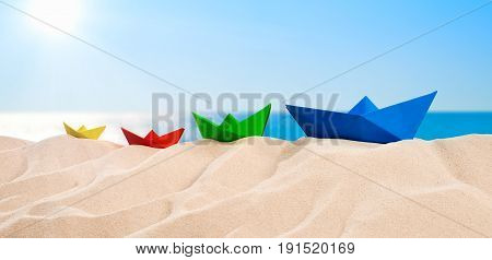 On the Beach - Sand dune with four colorful paper boats in front of beautiful azure sea on a sunny day On the Beach - Four colorful paper boats on a sand dune in front of the beautiful sea on a sunny day