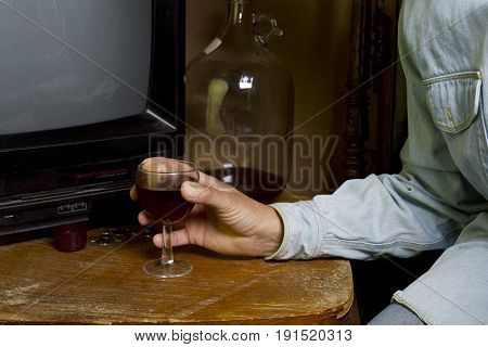 Man sitting in a living room with a glass of alcohol next to a TV set. Concept of loneliness