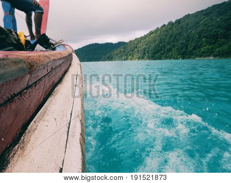 Beside View. Longtail Boat While Cruising On Sea Have Sea Water Splashing Beside It. Have Island And