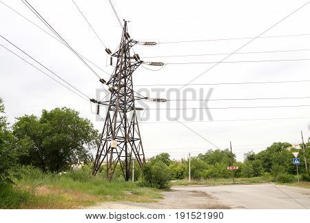 Old rusty mast of power lines on the city street