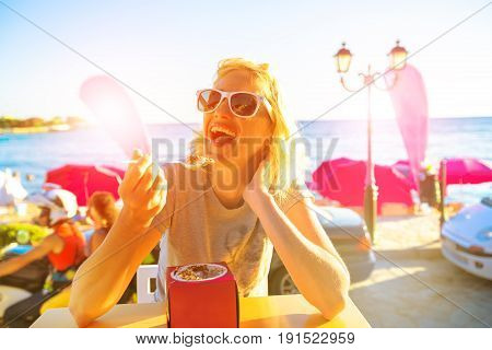 Healthy lifestyle woman eating typical Greek yogurt at seaside in Koroni Beach, Peloponnese, Greece.