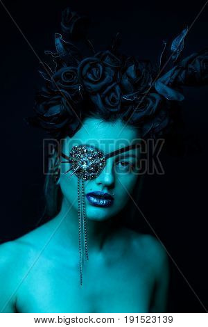 portrait of beautiful young woman with patch on eye and black flowers on head in blue studio light